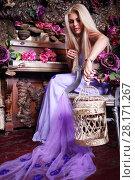 Купить «Pretty blonde woman in dress holds bird cage near piano in studio with flowers», фото № 28171267, снято 27 ноября 2015 г. (c) Losevsky Pavel / Фотобанк Лори