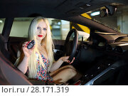 MOSCOW - MAY 20, 2016: Beautiful woman (with mr) sits at Lamborghini Huracan LP 610-4. Lamborghini Huracan is world first production car, using inertial navigation system. Редакционное фото, фотограф Losevsky Pavel / Фотобанк Лори