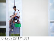 Купить «Young man hangs on safety cable and cleans window of high building», фото № 28171331, снято 12 июля 2016 г. (c) Losevsky Pavel / Фотобанк Лори