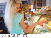 Купить «Beautiful woman smiles and holds funny calf of lion near showcase in cafe», фото № 28171375, снято 13 июля 2016 г. (c) Losevsky Pavel / Фотобанк Лори