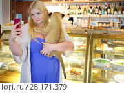 Купить «Young woman holds funny calf of lion in cafe and makes selfie», фото № 28171379, снято 13 июля 2016 г. (c) Losevsky Pavel / Фотобанк Лори