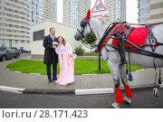 Купить «Happy couple pose near coach with horse near residential buildings», фото № 28171423, снято 17 сентября 2016 г. (c) Losevsky Pavel / Фотобанк Лори