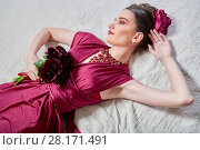 Купить «Young woman with bunch of flowers lies on bed, view from above», фото № 28171491, снято 9 декабря 2015 г. (c) Losevsky Pavel / Фотобанк Лори
