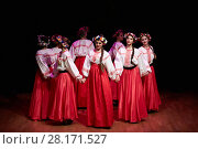 MOSCOW, RUSSIA - MAY 21, 2016: Girls in red skirts, embroidered white blouses and with wreaths on their heads dance Russian folk dance during concert of dance studio Firebird in Bogorodskoye. Редакционное фото, фотограф Losevsky Pavel / Фотобанк Лори