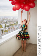 Купить «Young red-haired woman looks upward at bunch of red balloons that she holds in hand standing at balcony of highrise building», фото № 28171583, снято 15 октября 2015 г. (c) Losevsky Pavel / Фотобанк Лори
