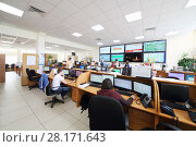 Купить «MOSCOW, RUSSIA - APR 25, 2016: Workers are sitting on workplaces with partitions near big screens in Moscow city telephone network», фото № 28171643, снято 25 апреля 2016 г. (c) Losevsky Pavel / Фотобанк Лори
