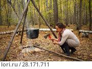 Купить «Woman chops wood near bonfire with hanging pot in yellow autumn forest», фото № 28171711, снято 18 октября 2015 г. (c) Losevsky Pavel / Фотобанк Лори