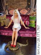 Купить «Pretty woman in dress sits on sofa and big snake is on floor indoor», фото № 28171767, снято 18 июля 2016 г. (c) Losevsky Pavel / Фотобанк Лори