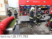 Купить «RUSSIA, MOSCOW - MAY 29, 2015: A man working with large tube near fire truck with equipment on territory of fire station», фото № 28171783, снято 29 мая 2015 г. (c) Losevsky Pavel / Фотобанк Лори