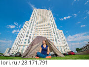 Купить «Smiling woman sits on grass near tent and tall buildings at sunny summer day», фото № 28171791, снято 18 июля 2016 г. (c) Losevsky Pavel / Фотобанк Лори