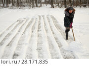 Купить «Smiling woman cleans outdoor skating rink surface from snow with shovel», фото № 28171835, снято 4 января 2016 г. (c) Losevsky Pavel / Фотобанк Лори