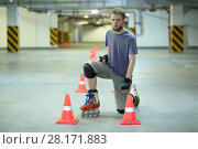 Купить «Roller skater poses on floor near orange cones in indoor parking», фото № 28171883, снято 22 октября 2015 г. (c) Losevsky Pavel / Фотобанк Лори