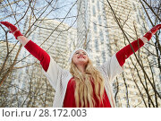 Купить «Young smiling woman stands in winter park near apartment buildings outstretching arms to sides», фото № 28172003, снято 15 января 2016 г. (c) Losevsky Pavel / Фотобанк Лори