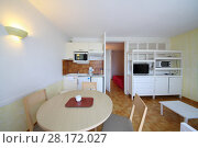 Купить «White lit kitchen with tv, refrigerator, microwave in modern hotel», фото № 28172027, снято 26 июля 2016 г. (c) Losevsky Pavel / Фотобанк Лори