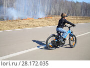 Купить «The little boy with the camera on his head goes on a bicycle on a road near a burning dry grass along the birch grove in the spring», фото № 28172035, снято 12 апреля 2015 г. (c) Losevsky Pavel / Фотобанк Лори