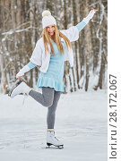 Купить «Young woman poses standing on one skate at outdoor skate rink in winter park», фото № 28172067, снято 19 января 2016 г. (c) Losevsky Pavel / Фотобанк Лори
