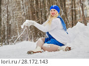 Купить «Plump smiling woman in skates sits in snowdrift and shakes off snow from mittens at outdoor skating rink in winter park», фото № 28172143, снято 19 января 2016 г. (c) Losevsky Pavel / Фотобанк Лори