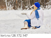 Купить «Plump smiling woman in skates sits in snowdrift and catches snowflakes on mitten at outdoor skating rink in winter park», фото № 28172147, снято 19 января 2016 г. (c) Losevsky Pavel / Фотобанк Лори