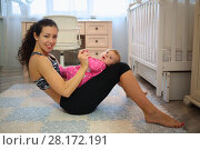 Купить «Happy mother sitting on the floor holding a baby on her knees», фото № 28172191, снято 4 октября 2016 г. (c) Losevsky Pavel / Фотобанк Лори