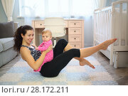 Купить «Mother with the baby in her arms sitting on the floor performs motion feet», фото № 28172211, снято 4 октября 2016 г. (c) Losevsky Pavel / Фотобанк Лори
