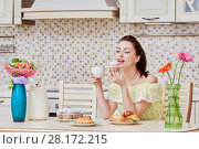 Young woman in yellow dress sits at table in kitchen, eats homemade cupcake and drink tea. Стоковое фото, фотограф Losevsky Pavel / Фотобанк Лори