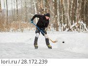 Купить «Hockey player at outdoor skating rink plays with puck», фото № 28172239, снято 21 января 2016 г. (c) Losevsky Pavel / Фотобанк Лори
