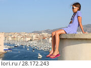 Купить «Girl sits on concrete on hill with views of old port Marseille, France», фото № 28172243, снято 30 июля 2016 г. (c) Losevsky Pavel / Фотобанк Лори