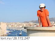 Купить «Boy in cap poses on concrete wall on hill with views of old port Marseille, France», фото № 28172247, снято 30 июля 2016 г. (c) Losevsky Pavel / Фотобанк Лори