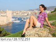 Купить «Pretty woman sits on hill near old port Marseille, France at sunny summer day», фото № 28172251, снято 30 июля 2016 г. (c) Losevsky Pavel / Фотобанк Лори