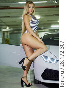 Купить «Young blonde woman in striped bodysuit and high-heel shoes poses near modern white car at underground parking», фото № 28172307, снято 2 июня 2016 г. (c) Losevsky Pavel / Фотобанк Лори