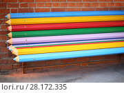 Купить «Street bench made from big multicolor pencils near brick wall on street», фото № 28172335, снято 30 октября 2015 г. (c) Losevsky Pavel / Фотобанк Лори