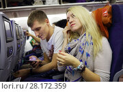 Купить «Man with smartphone and woman with headphones sit in airplane before flight», фото № 28172359, снято 1 ноября 2015 г. (c) Losevsky Pavel / Фотобанк Лори