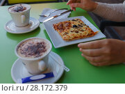 Купить «Two cappuccino and slice of pizza on plate on green table in cafe», фото № 28172379, снято 2 августа 2016 г. (c) Losevsky Pavel / Фотобанк Лори