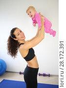 Купить «Mother in sportswear standing picks up baby near in the gym», фото № 28172391, снято 5 октября 2016 г. (c) Losevsky Pavel / Фотобанк Лори