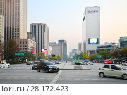 Купить «SEOUL - NOV 2, 2015: Wide avenue Sejong with driving cars, buses and highrise building among. South Korea is implementing road signs for dependent smartphones», фото № 28172423, снято 2 ноября 2015 г. (c) Losevsky Pavel / Фотобанк Лори