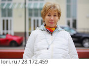 Купить «Elderly blonde woman in white jacket sits on bench outdoor, shallow dof», фото № 28172459, снято 6 октября 2016 г. (c) Losevsky Pavel / Фотобанк Лори