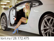 Купить «Slim blonde woman in yellow dress sits on driver seat of modern white car at underground parking», фото № 28172475, снято 2 июня 2016 г. (c) Losevsky Pavel / Фотобанк Лори