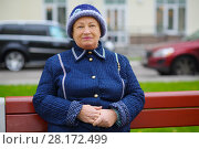 Купить «Elderly woman sits on bench near building at autumn day, shallow dof», фото № 28172499, снято 6 октября 2016 г. (c) Losevsky Pavel / Фотобанк Лори