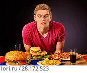 Купить «Student consume fast food», фото № 28172523, снято 15 октября 2015 г. (c) Gennadiy Poznyakov / Фотобанк Лори