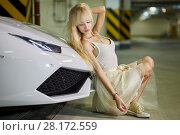 Купить «Young blonde woman sits leaning back to front bumper of modern white car at underground parking», фото № 28172559, снято 2 июня 2016 г. (c) Losevsky Pavel / Фотобанк Лори