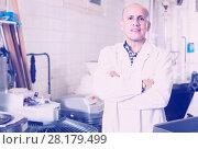 Купить «Worker standing near table in manufacture», фото № 28179499, снято 22 апреля 2017 г. (c) Яков Филимонов / Фотобанк Лори