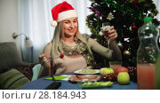 Купить «Young woman is sitting with champagne in New Year night at home.», видеоролик № 28184943, снято 12 февраля 2018 г. (c) Яков Филимонов / Фотобанк Лори