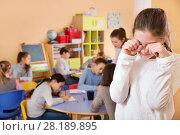 Купить «Upset girl in schoolroom on background with pupils», фото № 28189895, снято 28 января 2018 г. (c) Яков Филимонов / Фотобанк Лори