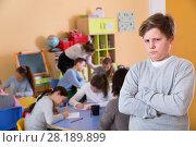 Купить «Portrait of upset boy in schoolroom on background with pupils st», фото № 28189899, снято 28 января 2018 г. (c) Яков Филимонов / Фотобанк Лори