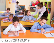 Купить «Portrait of young teacher woman at lesson with diligent school kids», фото № 28189919, снято 28 января 2018 г. (c) Яков Филимонов / Фотобанк Лори