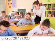 Купить «Teacher woman helping children during lesson in schoolroom», фото № 28189923, снято 28 января 2018 г. (c) Яков Филимонов / Фотобанк Лори