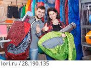 Купить «Young couple demonstrating tourist equipment», фото № 28190135, снято 8 марта 2017 г. (c) Яков Филимонов / Фотобанк Лори