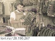 Купить «Male customer choose bulletproof vest», фото № 28190267, снято 4 июля 2017 г. (c) Яков Филимонов / Фотобанк Лори
