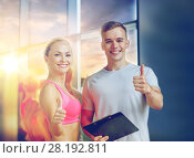 Купить «smiling young woman with personal trainer in gym», фото № 28192811, снято 29 июня 2014 г. (c) Syda Productions / Фотобанк Лори