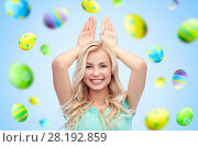 Купить «happy woman making bunny ears over easter eggs», фото № 28192859, снято 13 февраля 2016 г. (c) Syda Productions / Фотобанк Лори